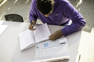 overhead shot of student with a laptop and writing in a notebook