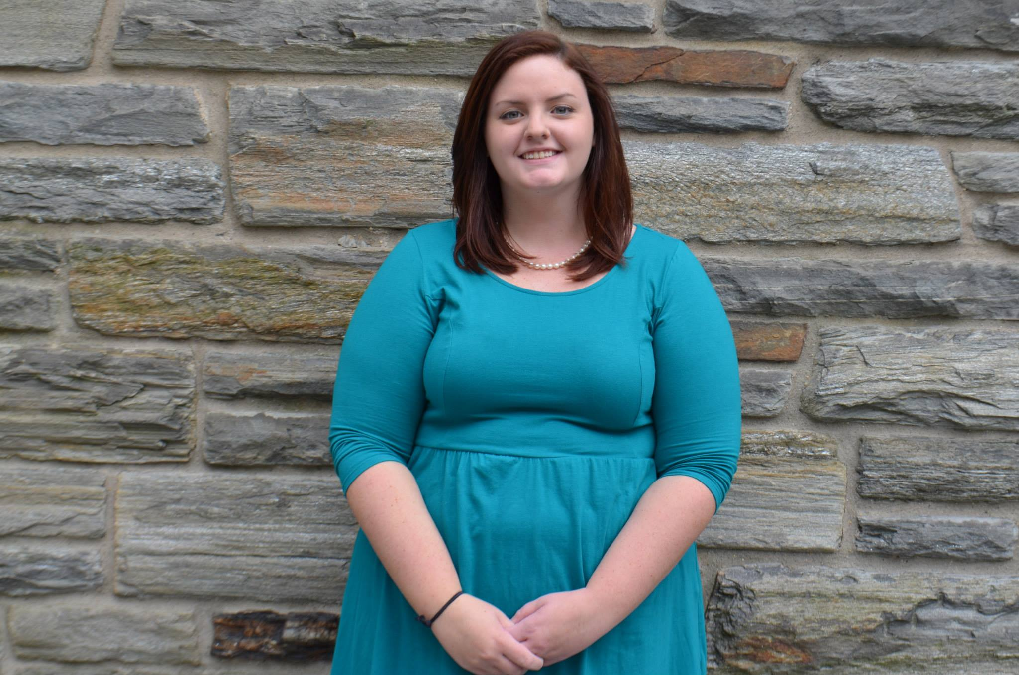 Corinne McGrath is standing in front of a stone wall. She is wearing a turquoise dress and a string of pearls.