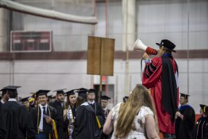 Ruben A. Mendoza, Ph.D., assistant professor of business intelligence and analytics and grand marshal, calls the graduates to order with his trusty bullhorn.