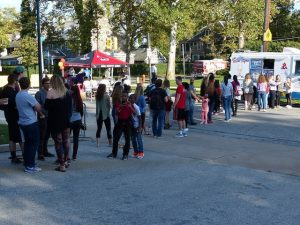 Students and neighbors line up for ice cream at the end of the block party.
