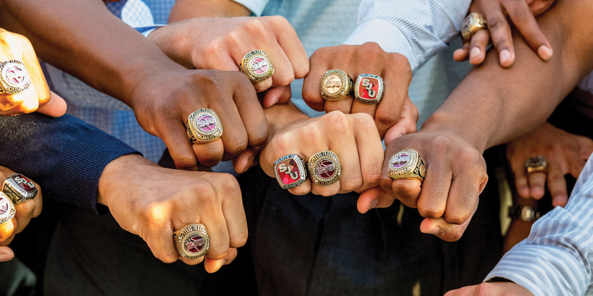 The Atlantic 10 men's basketball champions flash their 2016 commemorative rings, featuring SJU displayed horizontally. Why do some have two rings? Six Hawks also played for the 2014 A10 Championship, represented on the bands showing SJU diagonally  Photo: Greg Carroccio '02, Sideline Photos