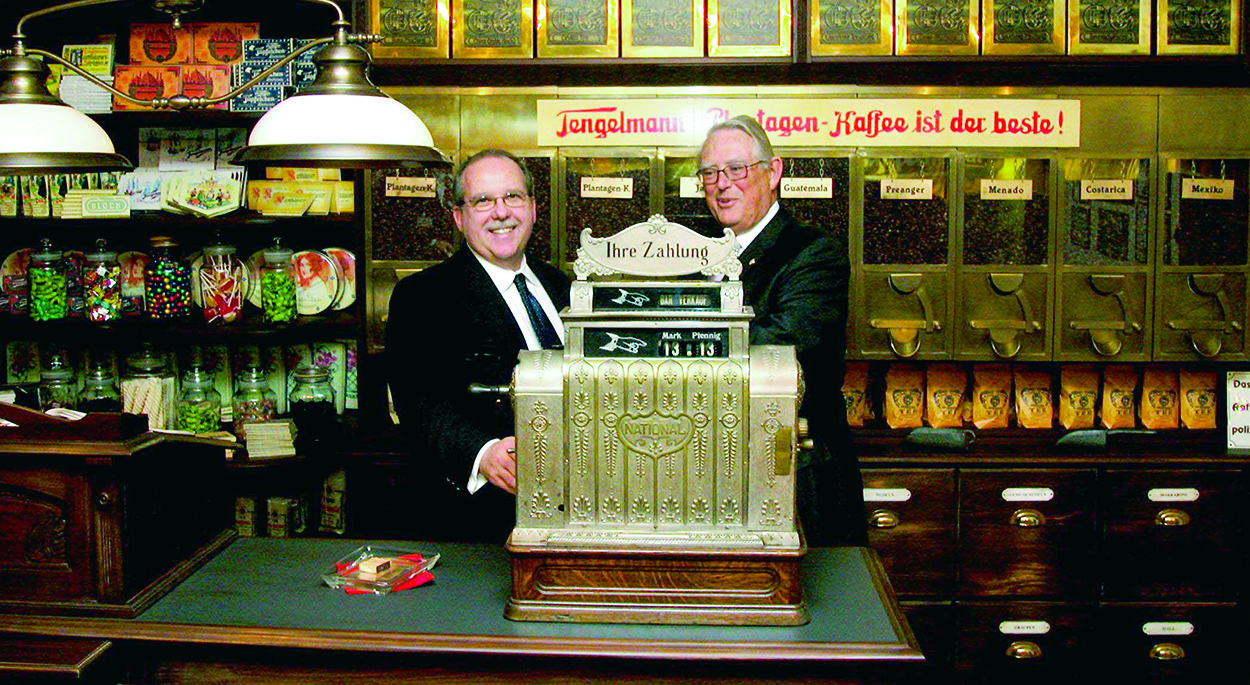 Dean DiAngelo and Erivan K. Haub pose with a register in a museum Haub built in 1995 at Tenglemann's headquarters in Germany to honor the company's rich heritage.