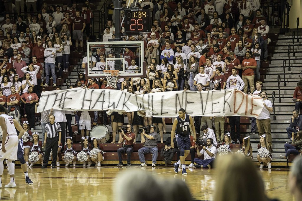 Hawks fan at basketball game with 'The Hawk Will Never Die' banner.