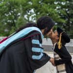 Rena Griggs in cap and gown kissing her daughter.