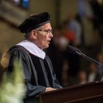 Don DiJulia in cap and gown gives commencement speech.