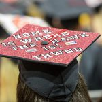 "A decorated graduation cap reads, ""Home is where the Hawk is! THWND"""