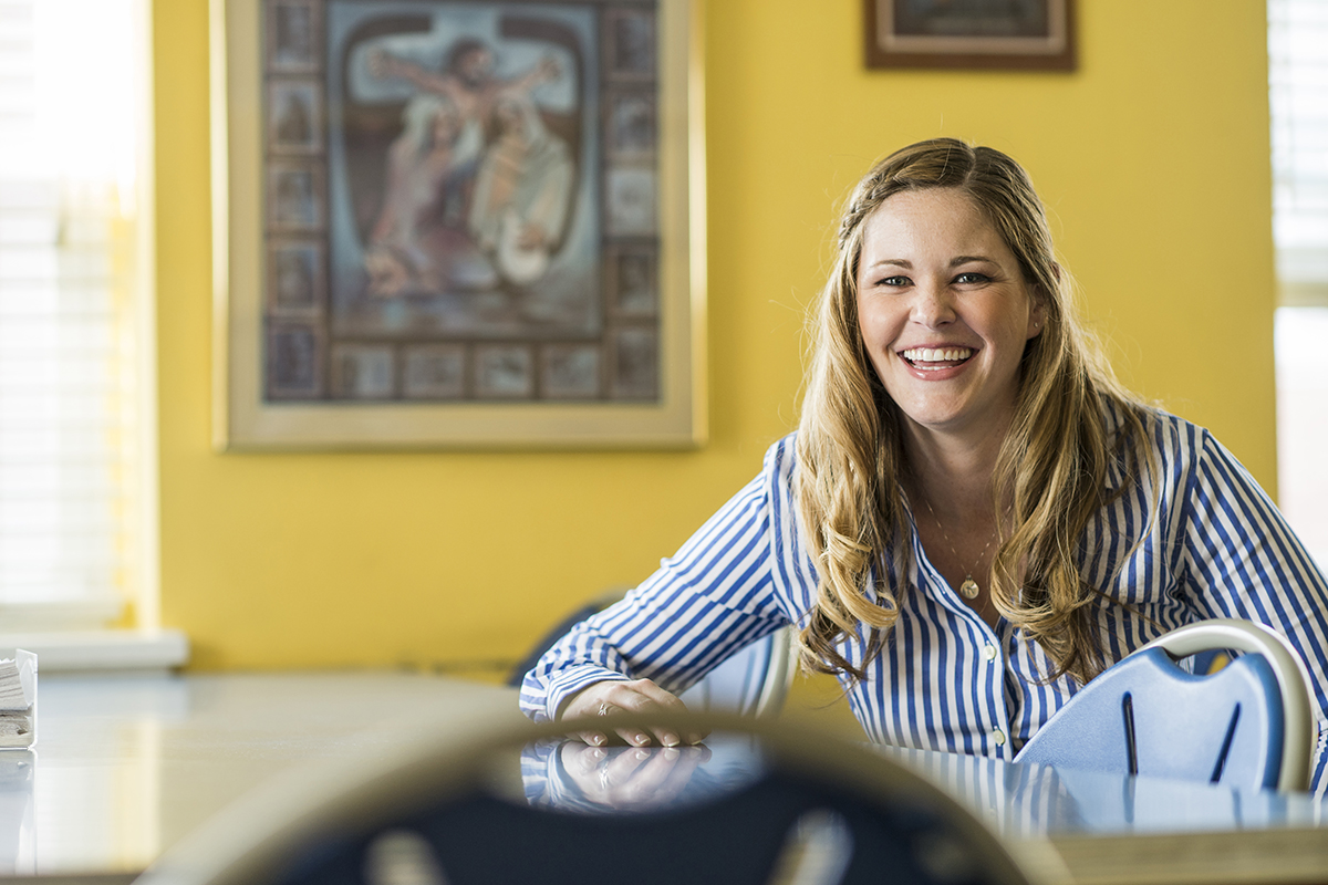 Kristin Prinn smiles at a table in front of a yellow wall background.