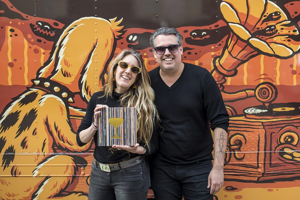 Tenaya and André Darlington are smiling with a vinyl in hand in front of their mobile record store, the Crosley Cruiser.