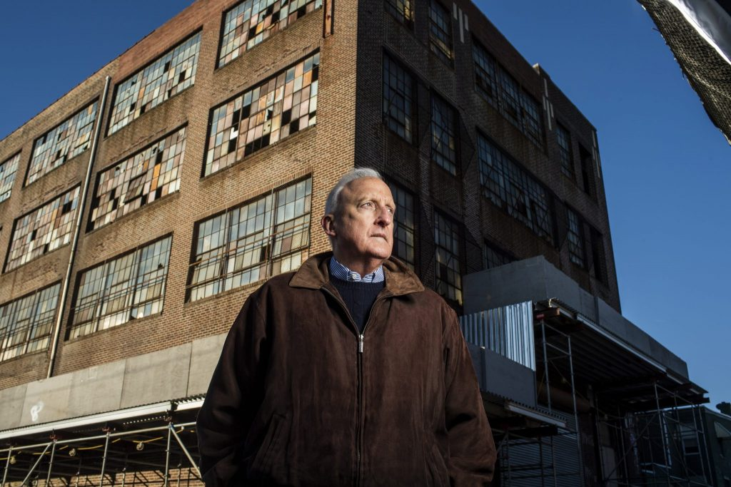 Peter Clark, dressed in a suede jacket, stands in front of the corner of a run-down building.