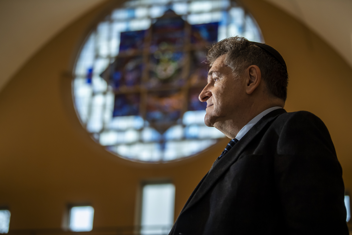 Rabbi Skorka stands in front of a stained glass window.