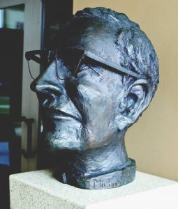 A sculpted bust of a priest - Michael J. Smith, S.J., wearing glasses.