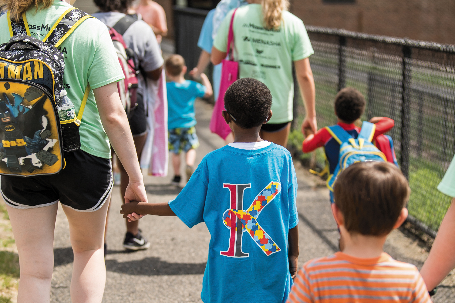 "A child wearing a Kinney ""K"" shirt holds hands with a young college student mentor."