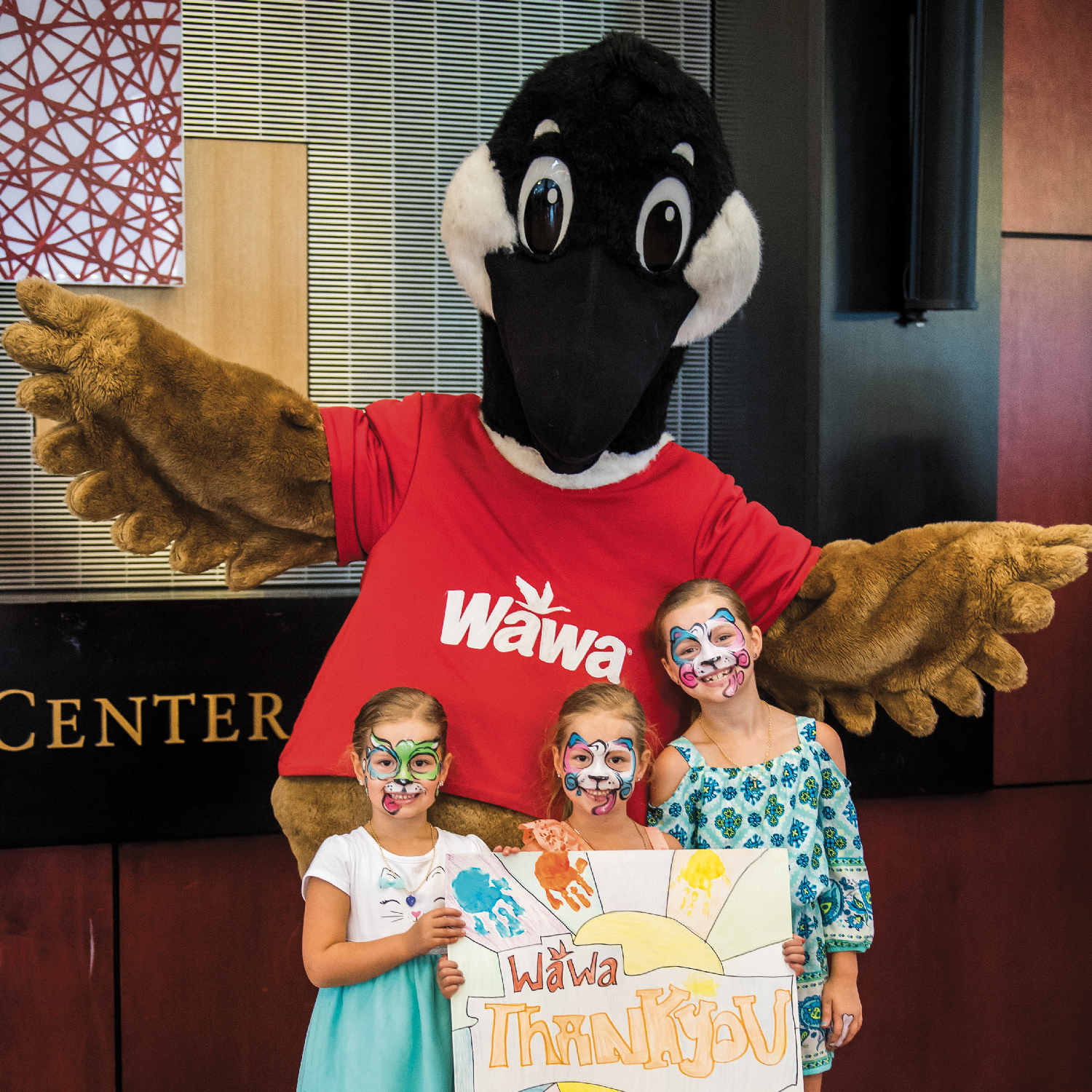 "The Wawa Goose poses with three young children holding a ""Thank You Wawa"" sign."
