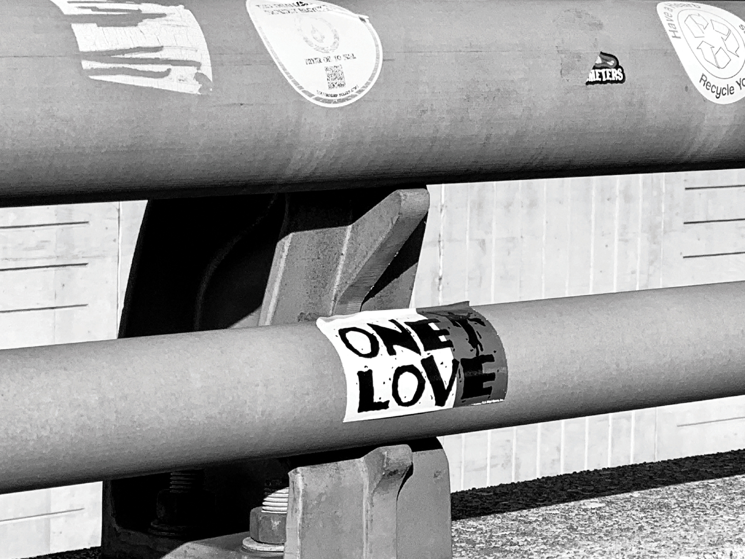 "A sticker reading ""One Love"" on a guardrail."