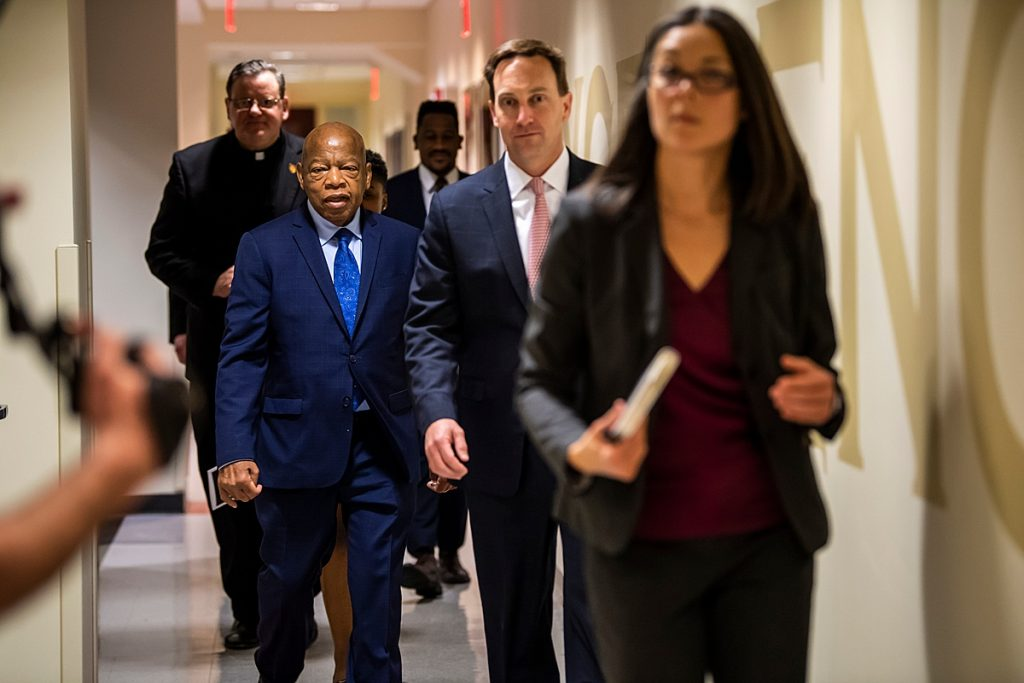 In a hallway that leads to the main floor of Hagan Arena, civil rights leader and congressman John Lewis walks with Associate Provost for Inclusion and Diversity Monica Nixon, Ed.D., University President Mark C. Reed, Ed.D., and Executive Director of Mission Programs Dan Joyce, S.J.