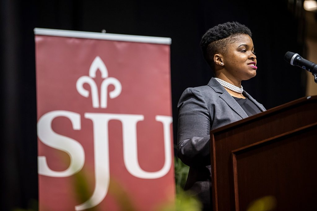 SJU student Taicha Morin'20 stands at a podium in Hagan Arena with an SJU banner behind her.