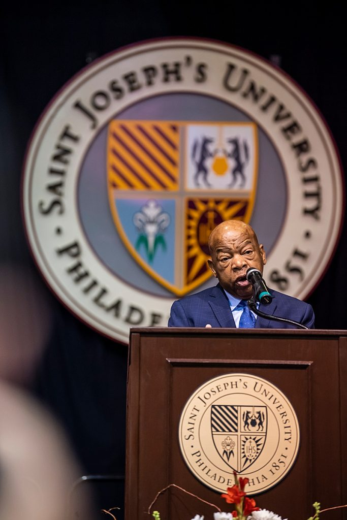 Civil rights leader and congressman John Lewis stands at a podium with the Saint Joseph's shield behind him.