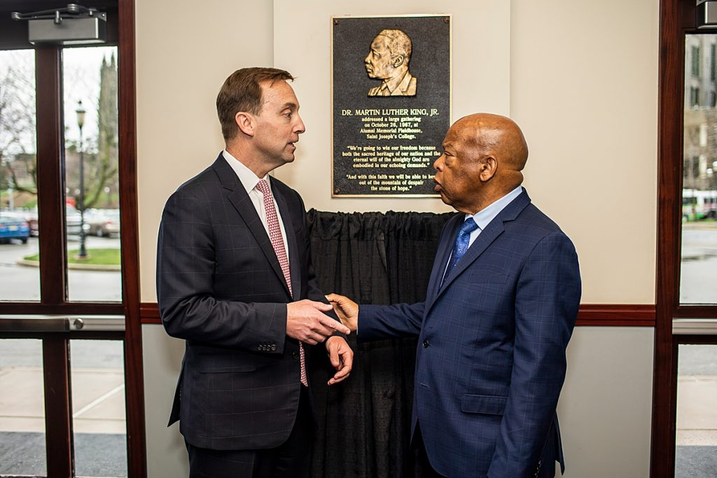 Dr. Reed and Lewis stand before a black and gold plaque that features an image of Dr. King