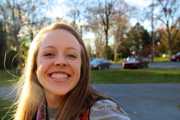 Grace Davis is smiling in front of a parking lot and trees with the sun shining on her cheek.