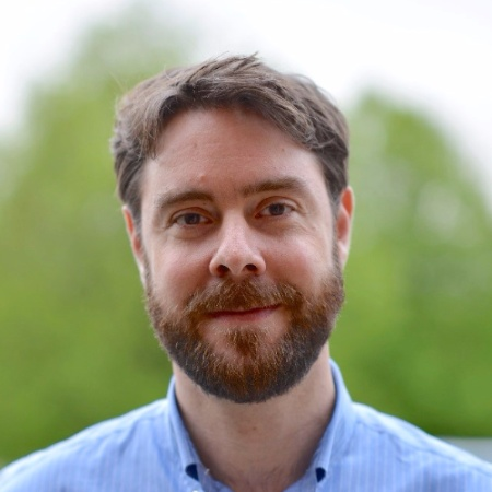David Henderson is standing in front of a blurred background of green trees. He has brown hair and a beard, and is wearing a blue shirt.