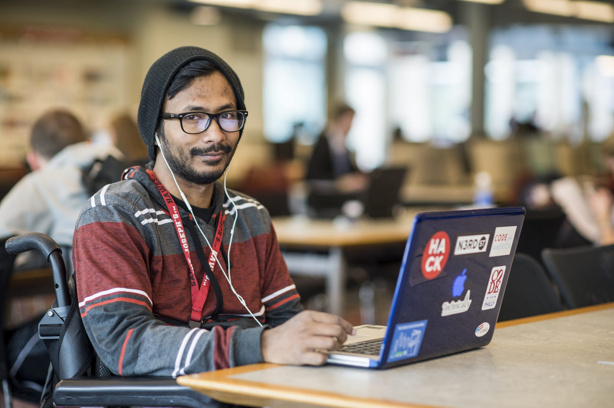 Ather Sharif is sitting in the library in front of his blue laptop covered in stickers. He is wearing a black beanie, striped hoodie, a lanyard, and has white earphones in his ears.