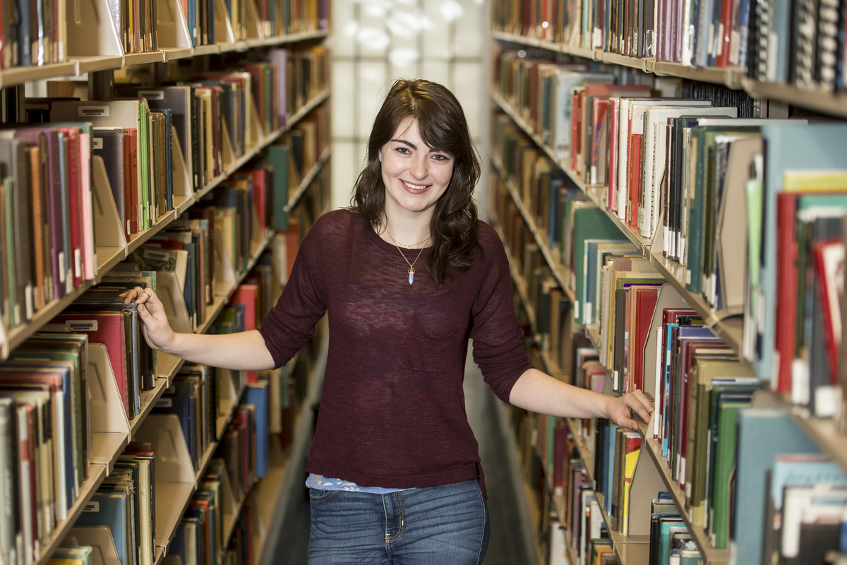 Brenna Ritzhart is walking between two library shelves full of books, her hands trailing along the volumes. She is wearing a dark red top, jeans, and a necklace.