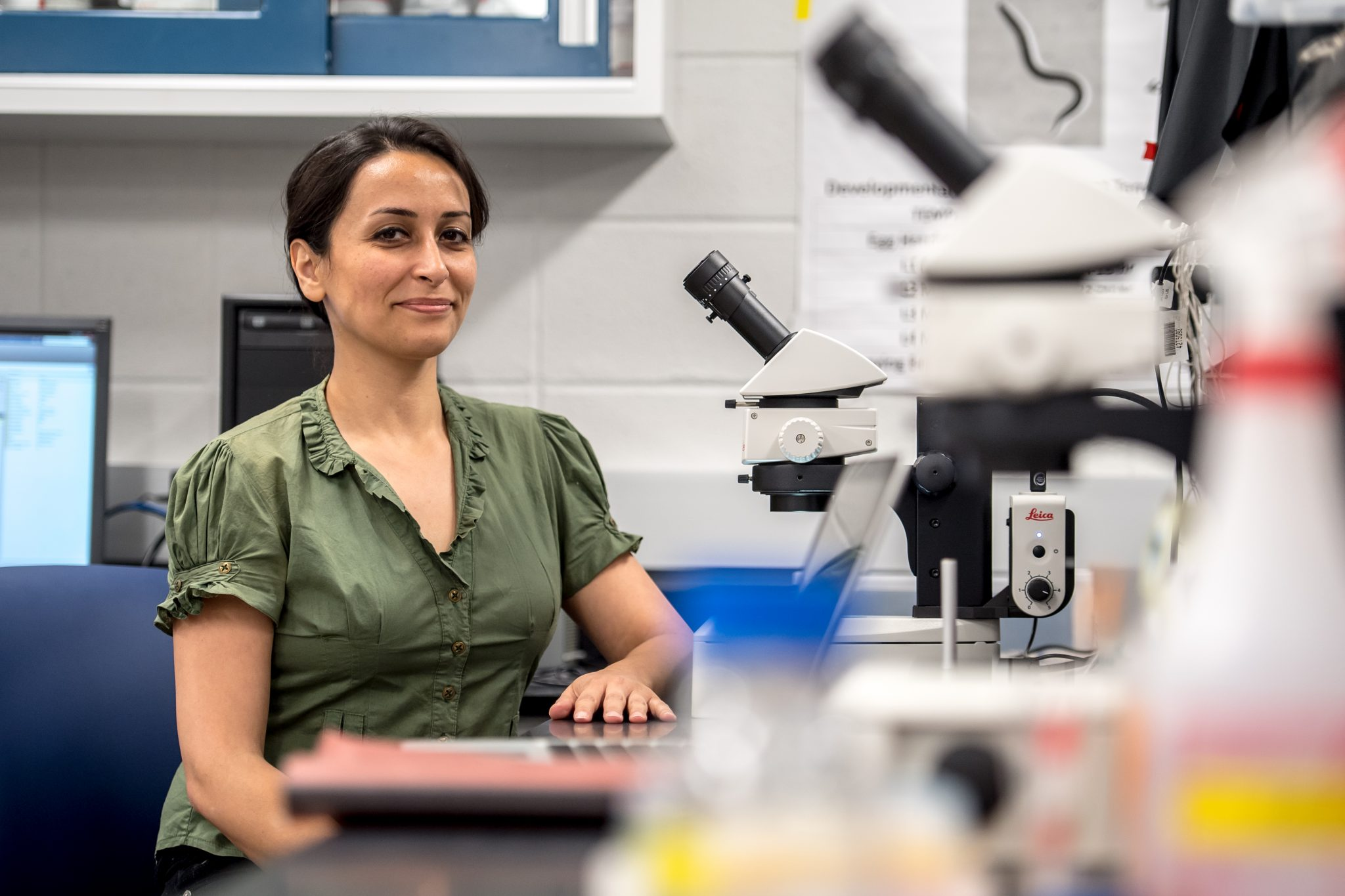 Niknaz Riazati is smiling at a lab bench behind two microscopes. She is wearing a green blouse and has her hair up.