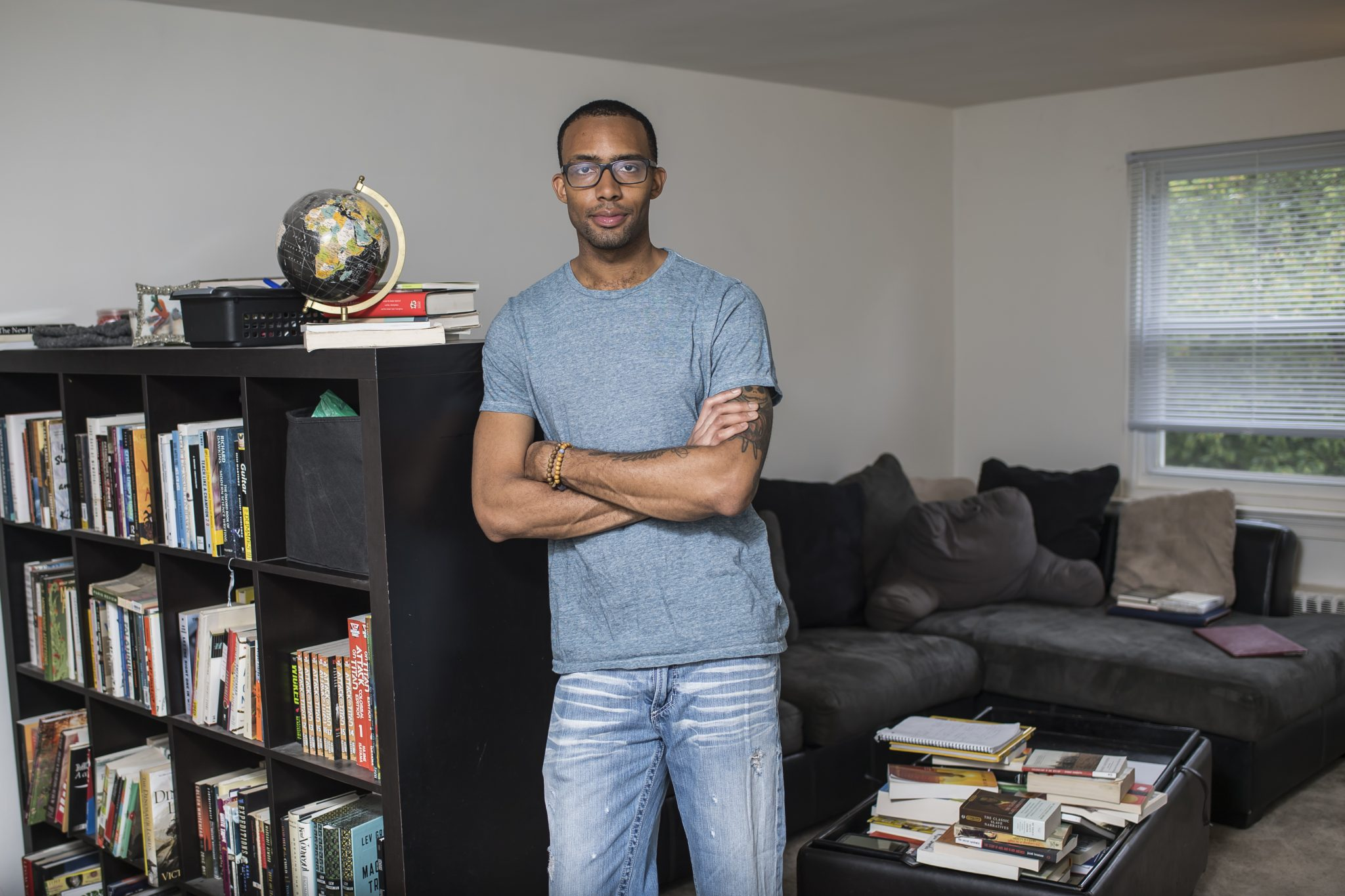 Joseph Thomas is leaning against a large bookshelf in a room filled with a big couch and various writing supplies. He is wearing a light grey shirt and jeans.