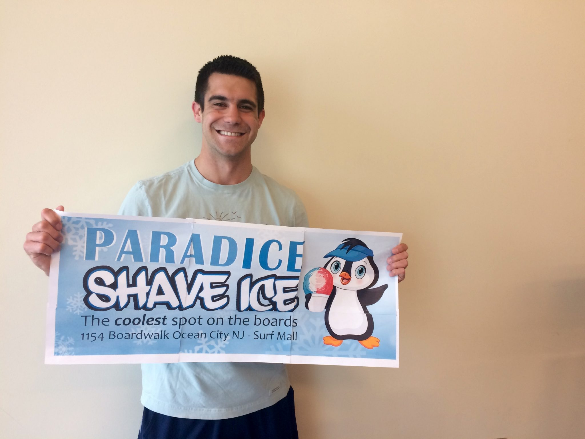"""Bobby Lattanzi is smiling and holding a sign with a small penguin with a visor that reads, """"Paradice Shave Ice."""""""