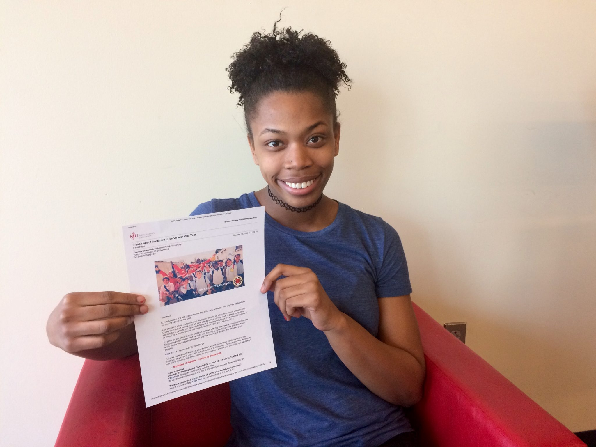 Brittany Stokes is sitting in a red chair, holding up her invitation to serve at City Year.