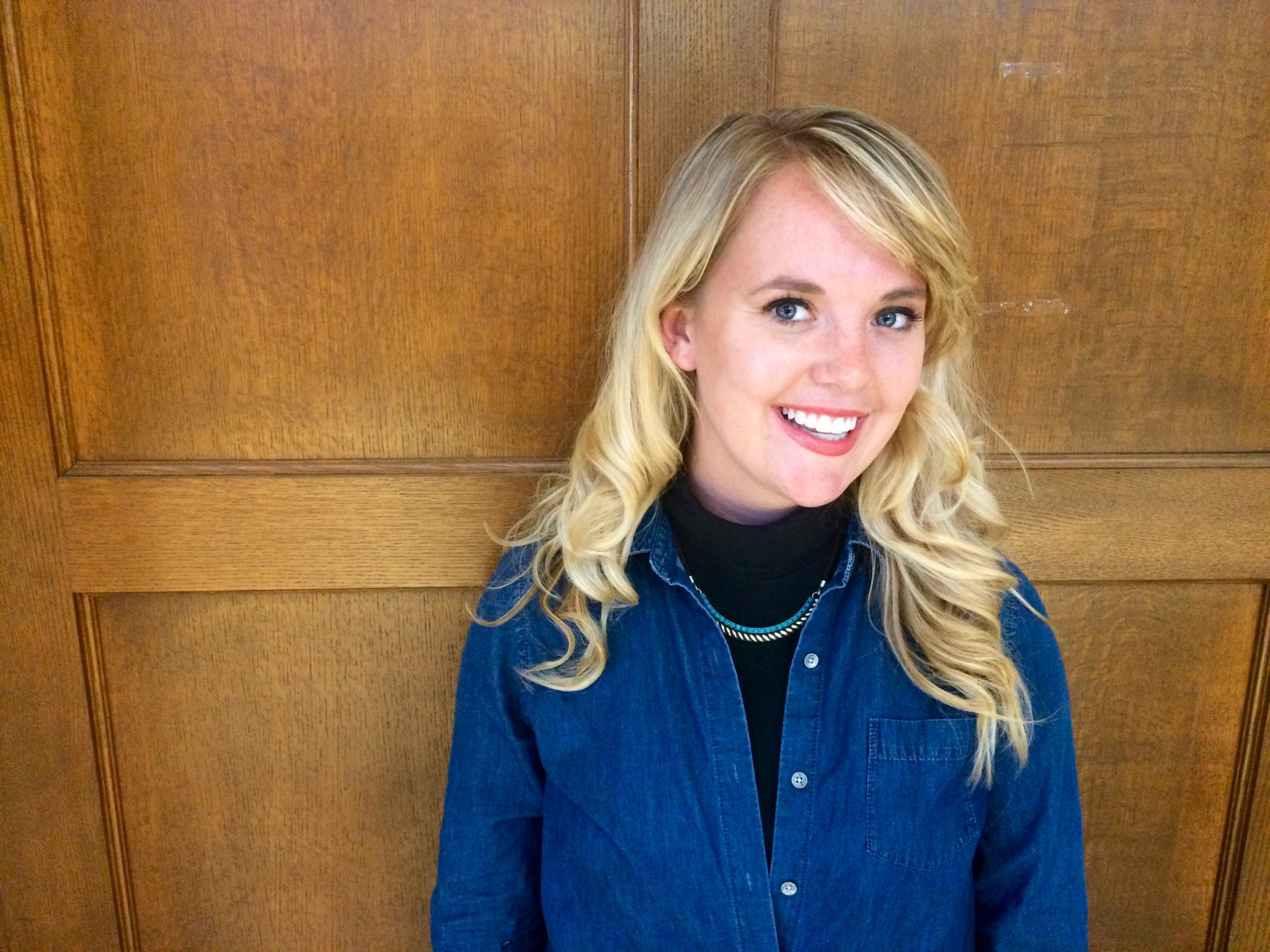 Clare Kocman is smiling in front of wooden panels. She is wearing a black turtlenecks with a blue top, and a teal and gold necklace.