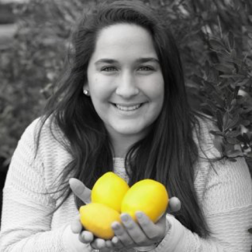 Ellie Paparone is smiling in a black and white photo. There are three yellow lemons in her hands.