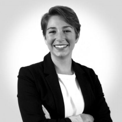 Emily Smedley is smiling, arms crossed, in a black and white photo. The gradient background is lightest around her.
