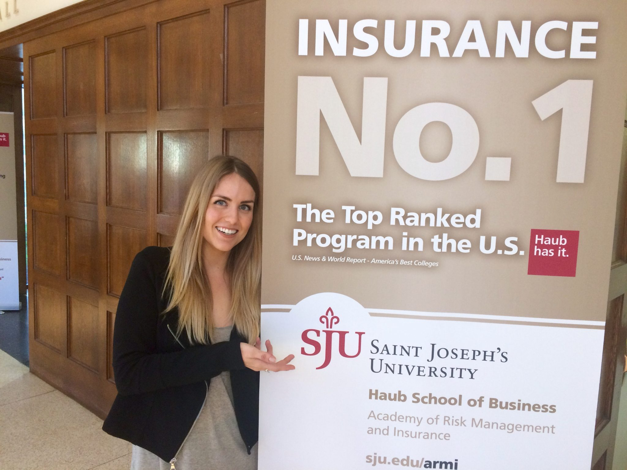 """Katie Boutin is pointing to a sign reading, """"Insurance No.1: The Top Ranked Program in the U.S.: Saint Joseph's University Haub School of Business."""""""