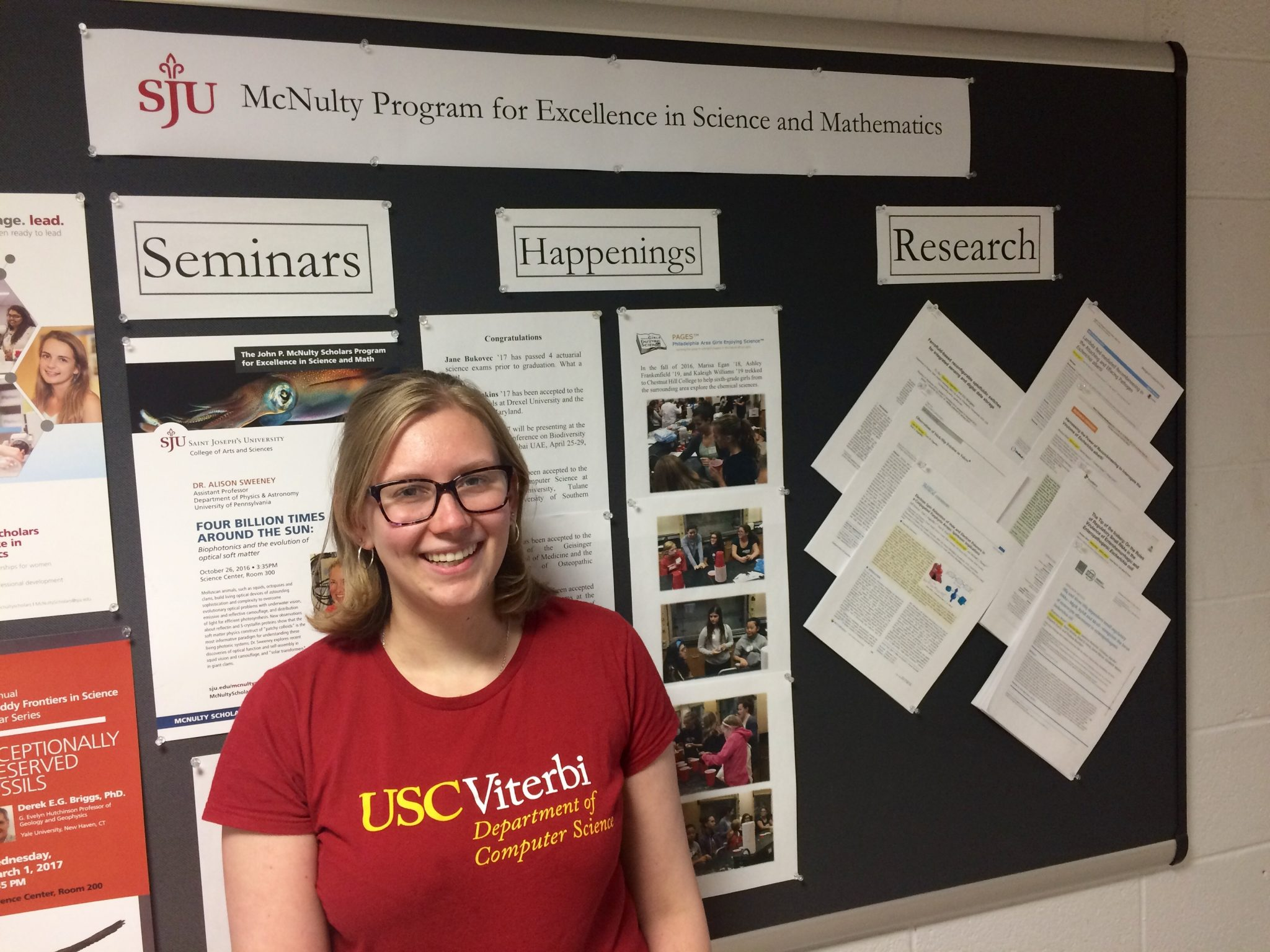 "Sarah Cooney is smiling in front of a board reading, ""SJU McNulty Program for Excellence in Science and Mathematics."" She is wearing a red shirt and glasses."