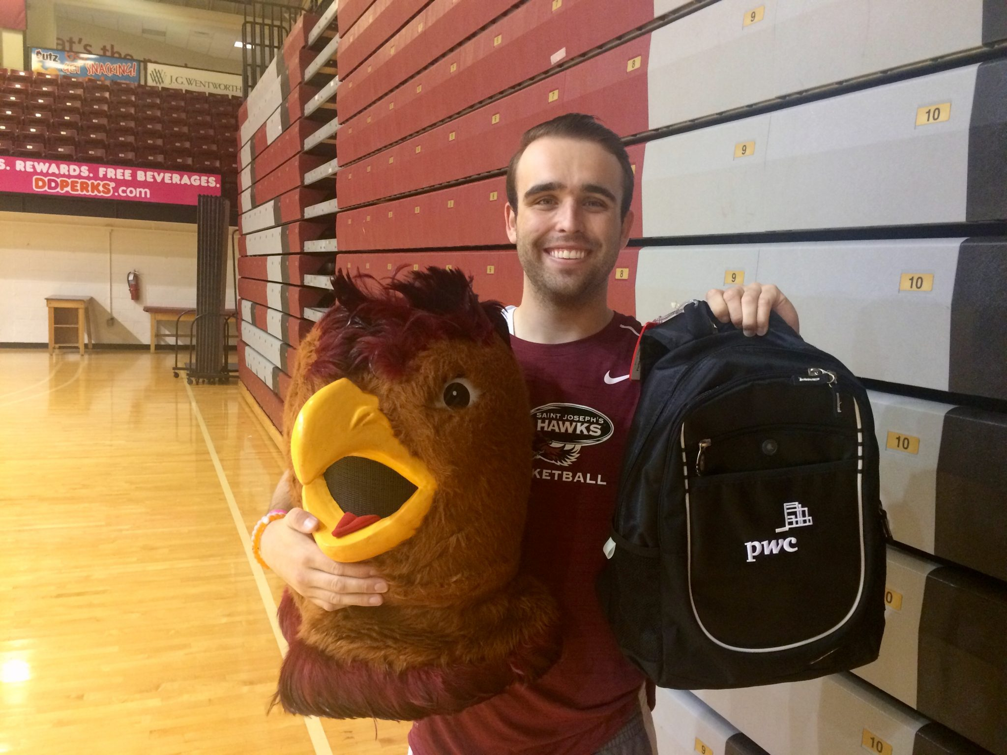 Timmy Parks is smiling in a gym, holding the Hawk mascot head and a PWC backpack.