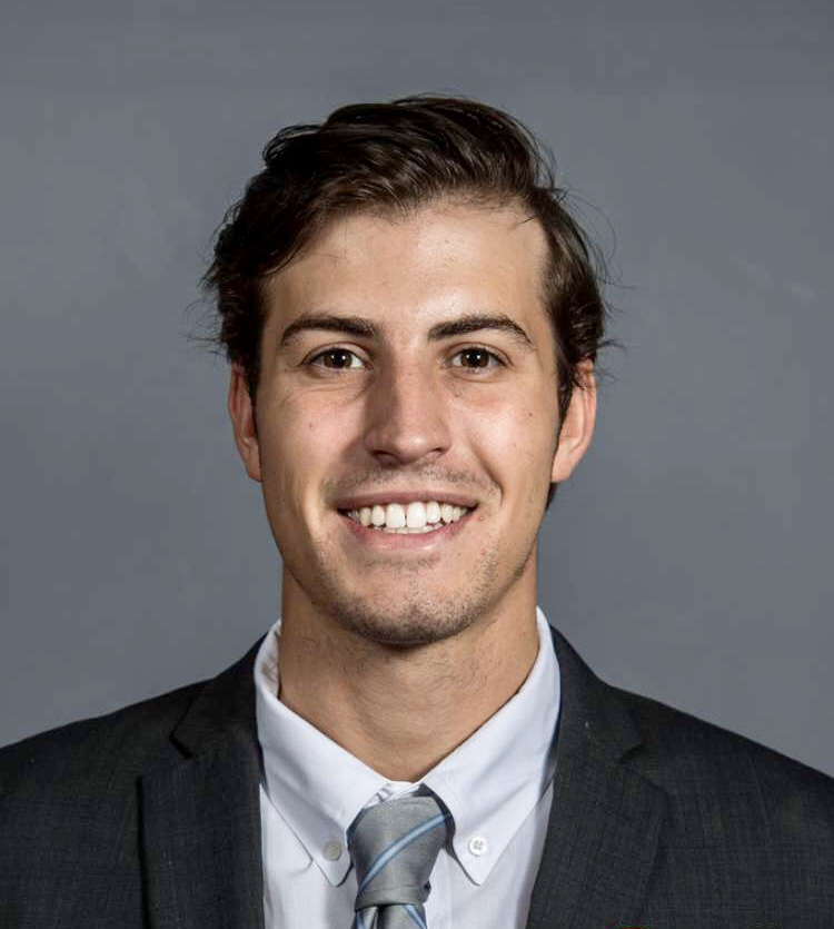 Harrison Zucco is smiling in front of a grey background. He is wearing a dark suit and a grey, striped tie.