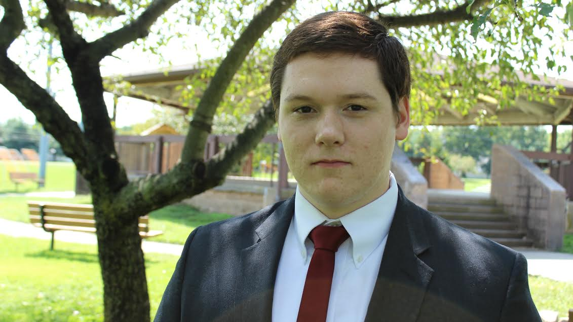 Kevin Furlong is a young man standing under a tree in a park. He is wearing a dark suit with a red tie.