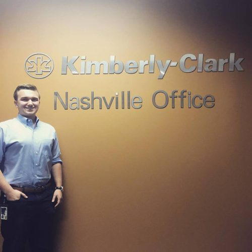 "Sean Maliga is standing against a wall that reads, ""Kimberly-Clark: Nashville Office."" He is wearing a pale blue shirt and slacks."