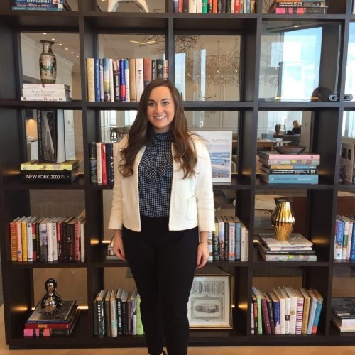 Kristin Thompson is standing in front of shelves filled with books, vases, and figurines. She is wearing a white blazer, check blouse, and black slacks.