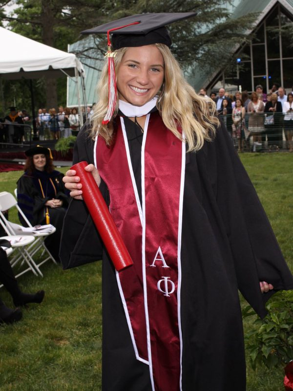 Katarina Weber is smiling in her graduation gown and cap in front of the Cardinal Foley Center. She is wearing a red Alpha Phi graduation stole.