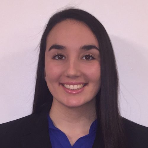 Kayla Cecchine is smiling in front of a pink wall. Her hair is dark and straight, and she is wearing a blue top with a dark blazer.