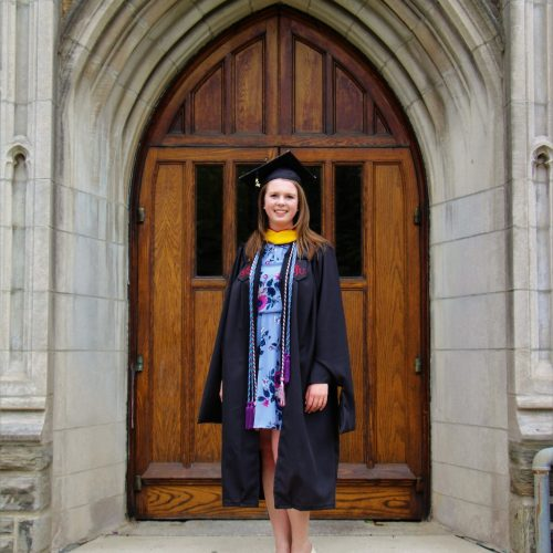 Daire Ryan is standing in front of an arched door from Barbelin. She is wearing a graduation cap and gown. She is wearing multiple honor cords, and a blue, floral dress.