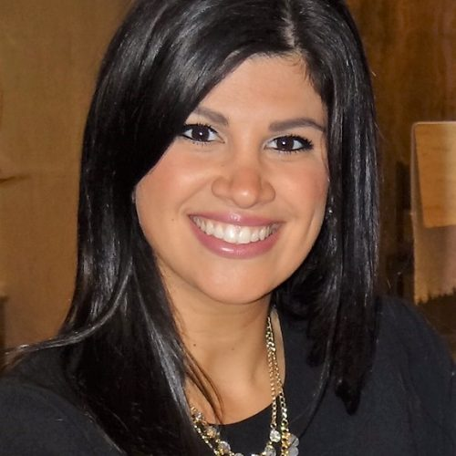Giana Alongi is smiling in front of a brown room. She is wearing a dark top and gold necklaces.