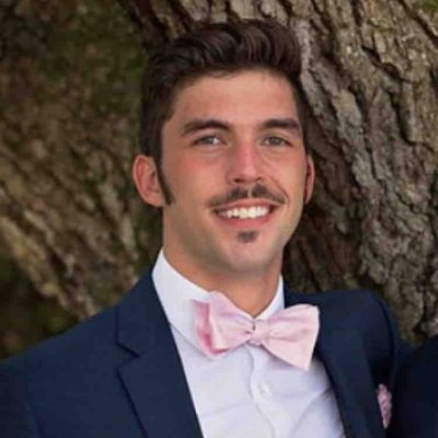 Michael Centanni is smiling under a tree. He is wearing a dark suit with a pink bowtie.