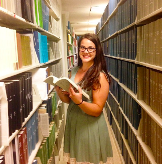 Katherine Grygo is standing between two library shelves, with a book opened in her hands. She is wearing a green dress and glasses.