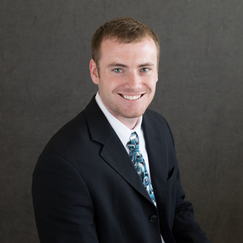 Corey MacDonald is facing the right, smiling in front of a dark background. He is wearing a dark suit with a patterned, teal tie.