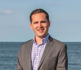 Jake Callahan is standing in front of the ocean. He is wearing a red and blue check shirt with a grey blazer.