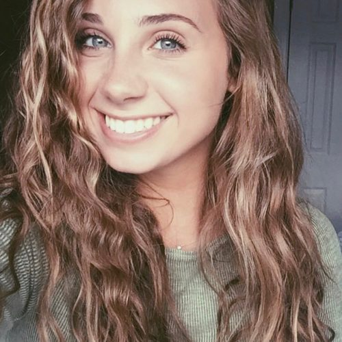 Alexa Sinatore has wavy, light hair and blue eyes. She is wearing a pale green top in a dimly lit room.