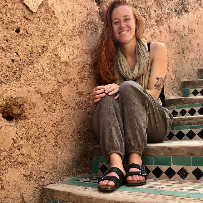 Beth Villanyi is smiling on tiled, outdoor steps. She is wearing loose clothing and sandals, with her hair parted to the side.